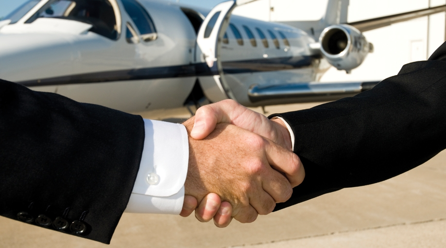 two pilots shaking hands that just purchased a plane